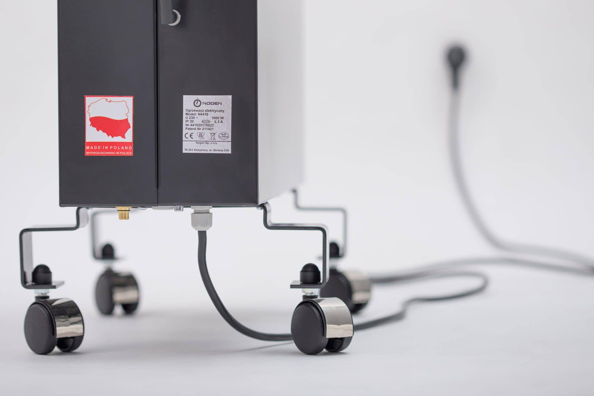 Grafitowy grzejnik NOGEN w wersji mobilnej na stopkach podłączony do zasilania.